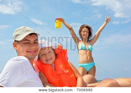 Young Man With Little Girl In Orange Lifejacket And Beautiful Woman With Plastic Toy Bucket