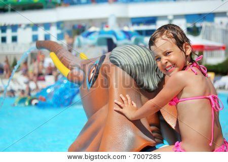 Little Girl Sitting On Toy Elephant Near Pool In Aquapark