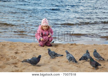 Little girl sits on beach at water edge in autumn day and feeds pigeons.
