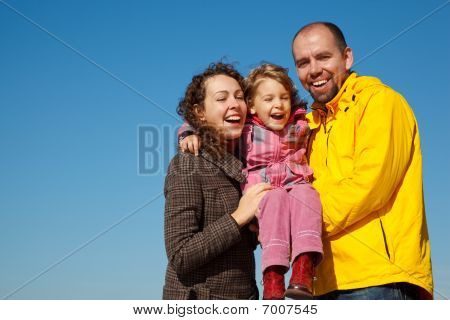 Happy parents together with daughter on hands bright sunny day against blue sky.