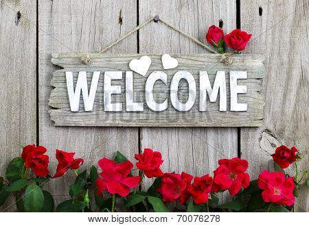 Flower border of red roses by wood welcome sign with hearts hanging on wooden fence