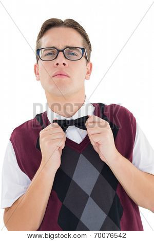 Nerdy hipster fixing his bow tie on white background