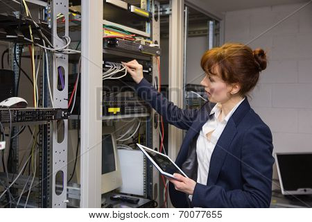 Pretty technician using tablet pc while fixing server in large data center