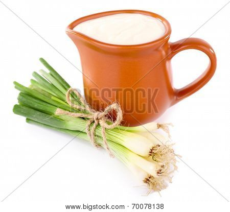 Clay pot with cream and a tuft of onion near it on white background isolated