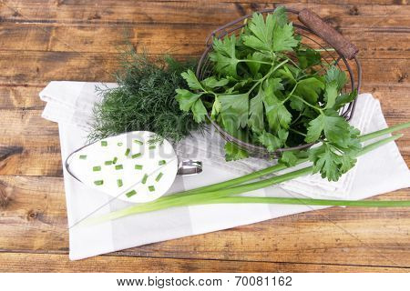 Metal bowl of cream with a tuft of onion, dill and parsley in a basket near it on a napkin on wooden background