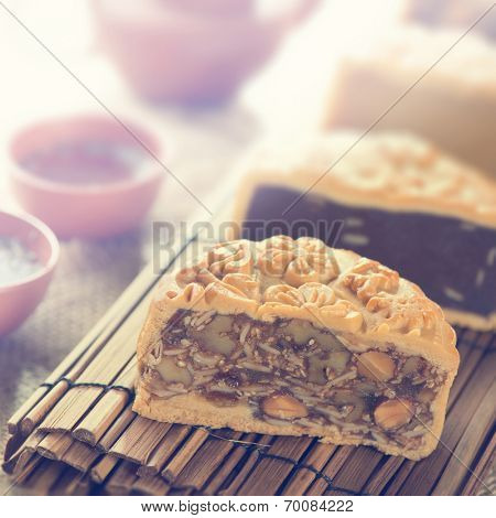 Traditional mooncakes on table setting with teacup. Retro vintage style Chinese mid autumn festival foods. The Chinese words on the mooncakes means assorted fruits nuts, not a logo or trademark.