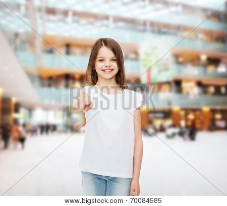 advertising, childhood, gesture, consumerism - smiling girl in white t-shirt pointing finger on you over shopping center background