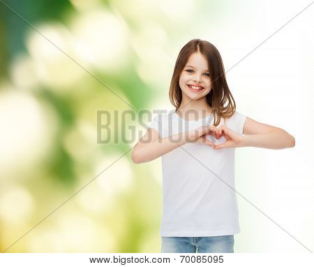 advertising, childhood, ecology, charity and people - smiling little girl in white t-shirt making heart-shape gesture over green background