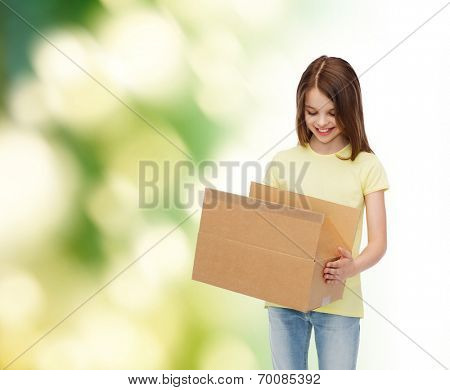 advertising, childhood, delivery, mail and people - smiling girl holding open cardboard box and looking into it over green background
