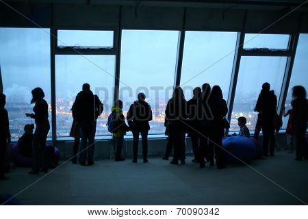 Silhouettes of many people on the background of a window with a view of the evening city