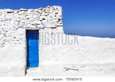 Blue door in whitewashed wall on Mykonos, Greece.