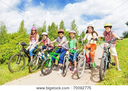 Row of kids diversity in helmets and bikes