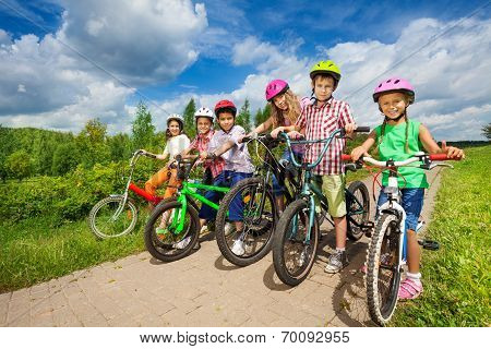 Children in row wearing helmets holding bikes