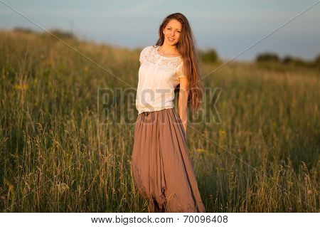Beautiful Long-haired Woman In A Skirt And White Blouse