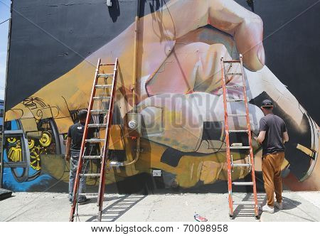 Street artists painting mural at Williamsburg in Brooklyn