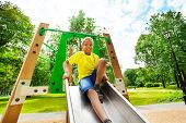 picture of chute  - Smiling boys with bending knee sitting on chute of playground - JPG