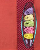 foto of glass noodles  - Colorful dried noodles in glass tray on red cloth background - JPG