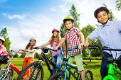 Постер, плакат: Row of happy children in bike colorful helmets