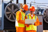 foto of substation  - electrical engineers using laptop computer in electric substation - JPG
