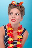 image of hawaiian girl  - Closeup top view portrait of beautiful emotional coquette girl with pretty smile in pinup style with Hawaiian flowers necklace amazed looking sideways isolated on blue - JPG
