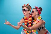 stock photo of hawaiian girl  - Full length portrait of two beautiful emotional coquette sexy girls with pretty smiles in pinup style with Hawaiian flowers necklaces - JPG