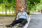 picture of accident victim  - A fat Asian guy sleeping under the tree beside the street - JPG