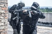 stock photo of anti-terrorism  - Two spec ops soldiers in black uniform in action