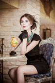 image of beautiful lady  - Fashionable attractive young woman in black dress sitting in restaurant - JPG