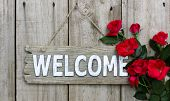 picture of wooden fence  - Rustic wood welcome sign with red roses hanging on wooden fence - JPG