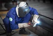 stock photo of pipe-welding  - Worker with protective mask welding metal in factory - JPG
