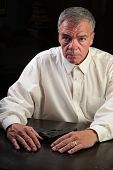 foto of button down shirt  - Middle age man in white button up shirt sitting at table with palms down  - JPG