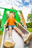 stock photo of chute  - Boy sits on metallic chute and ready to slide in playground - JPG