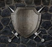 stock photo of crossed swords  - Medieval shield and crossed swords on stone wall - JPG