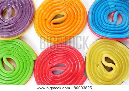 some licorice wheels of different colors on a white background