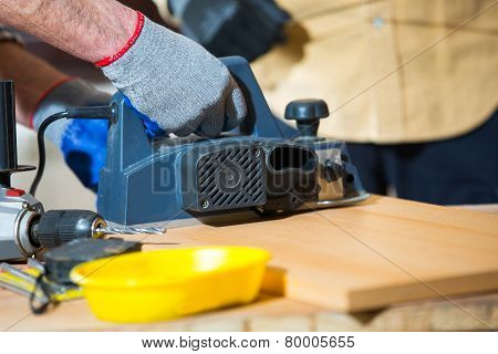 Home improvement - handyman sanding wooden floor in workshop
