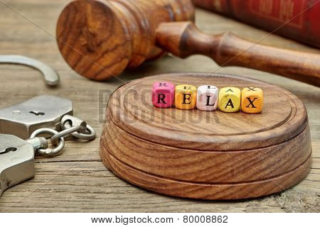 Sign Relax On The Soundboard, Judges Gavel, Handcuffs And Book In The Background