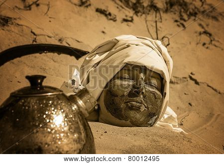 woman portrait and teapot with water on a sand