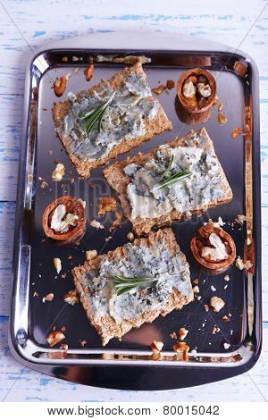 Crispbread with blue cheese and sprigs of rosemary on metal tray and color wooden table background