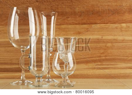 Empty goblets on wooden background