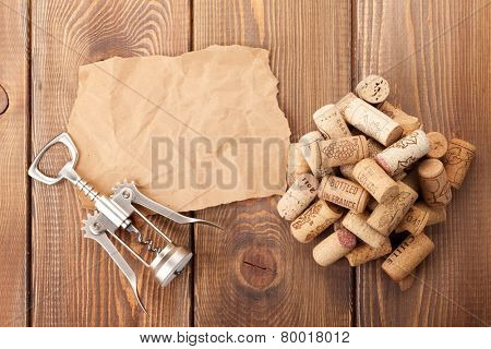 Wine corks and corkscrew over rustic wooden table background. View from above with piece of paper for copy space
