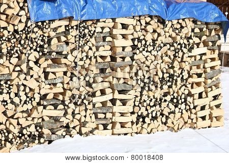 Woodshed With Pieces Of Wood Piled Up For The Winter And Snow