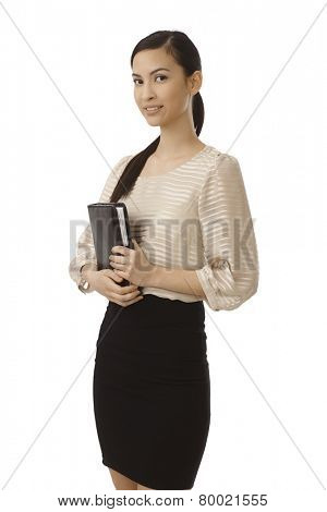 Young Asian businesswoman holding personal organizer, smiling.