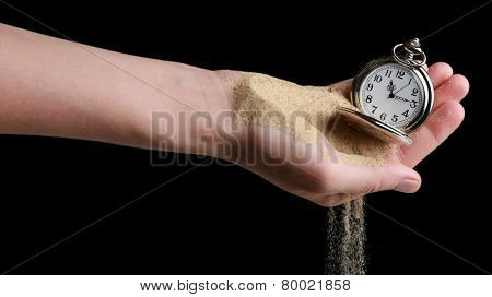 Silver pocket clock in hands and sand flowing away on black background