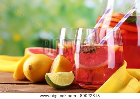 Pink lemonade in glasses and pitcher on table on natural background