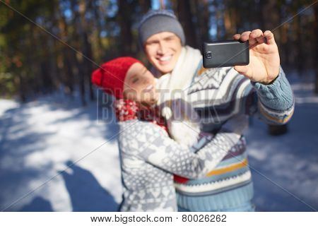 Amorous young couple making their selfie in natural environment