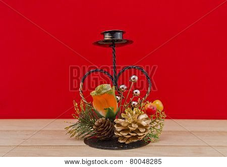 Heart-shaped  iron support  for pillar candle against red background