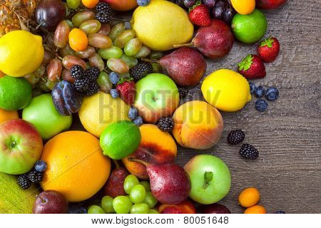 Mix of Colorful Fruits  with water drops on dark wooden table background