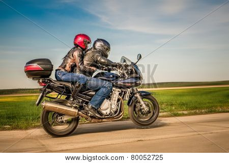 RUSSIA-JULY 7, 2013: Man and woman on a Suzuki Bandit bike doing wheelies. Suzuki Bandit is a series of sport-standard motorcycles. Suzuki Motor Corporation is a Japanese multinational corporation.
