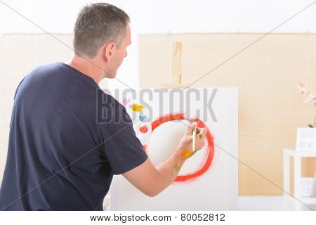 Artist painting holding paintbrush with artist palette, canvas on easel in a background