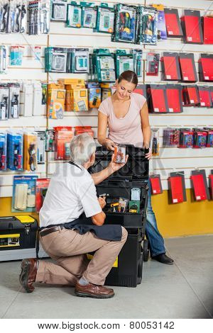 Full length of senior salesman assisting female customer in hardware store